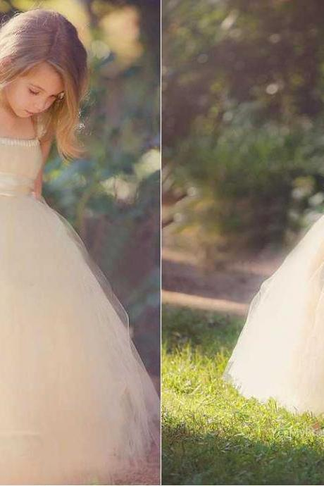 Floor length custom flower girl dress. Blush tulle puffy ball gown skirt adds dimension for a stunning look. Sleeveless spaghetti strap bodice features gathered details neckline and delicate flower at ribbon adorning on empire waist and perfectly tied at back
